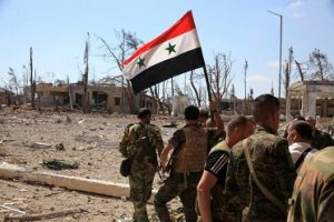 Forces loyal to Syria's President Bashar al-Assad walk at a military complex as one of them holds up a Syrian national flag, after they recaptured areas in southwestern Aleppo on Sunday that rebels had seized last month, Syria, in this handout picture provided by SANA on September 5, 2016. SANA/Handout via REUTERS/File Photo ATTENTION EDITORS - THIS PICTURE WAS PROVIDED BY A THIRD PARTY. REUTERS IS UNABLE TO INDEPENDENTLY VERIFY THE AUTHENTICITY, CONTENT, LOCATION OR DATE OF THIS IMAGE. FOR EDITORIAL USE ONLY.