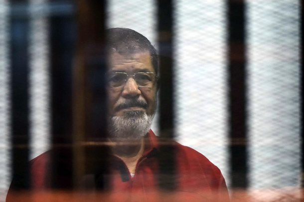 Egypt's ousted Islamist president Mohamed Morsi, wearing a red uniform, stands behind the bars during his trial in Cairo on June 21, 2015. AFP PHOTO / STR