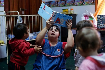 """Noelia Garella (C), a kindergarten teacher born with Down Syndrome, reads a book to children at the Jeromito kindergarten in Cordoba, Argentina on September 29, 2016. When Noelia Garella was a child, a nursery school rejected her as a """"monster."""" Now 31, she is in a class of her own. In the face of prejudice, she is the first person with Down syndrome to work as a kindergarten teacher in Argentina -- and one of few in the world. / AFP PHOTO / DIEGO LIMADIEGO LIMA/AFP/Getty Images"""